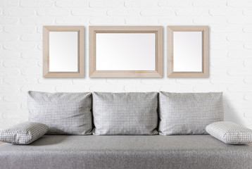 Interior decor mock up, Three blank wooden photo frames on white bricks  textured wall over modern couch