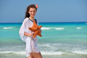 Young beautiful woman in white dress and seastar on the beach