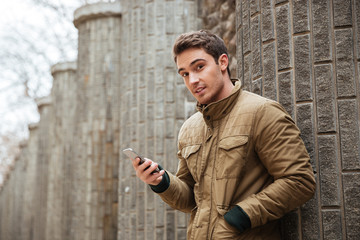 Attractive man chatting by his phone outdoors.
