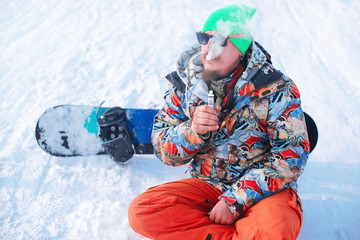 snowboarder resting on ski slope, vaping Electronic Cigarette ,winter sports concept. Close-up