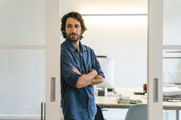 Businessman leaning at office door with arms crossed