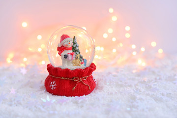 A snow globe with snowman on snow and Christmas lights. A Festive Christmas background