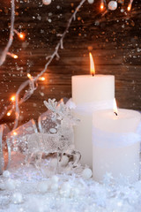 Two burning candles with a deer on snow and Christmas lights. Christmas decorations on wooden background. Festive Christmas background
