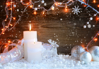 Two burning candles with a deer with christmas decorative balls on snow and Christmas lights. Christmas decorations on wooden background. Festive Christmas background