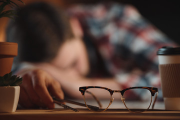 Cropped image of tired designer sleeping in office near glasses