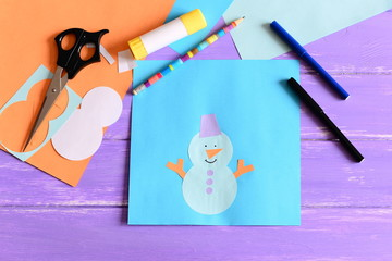 Making a children winter paper cards. Step. Paper snowman applique, scissors, markers, pencil, glue stick, colored paper set, snowman templates on wooden table. Kids winter crafts project. Top view