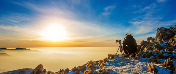 Professional photographer takes photos with camera on tripod on Deogyusan mountains, South Korea.