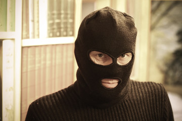 Thief in mask wants to rob the House. He is resolute. Portrait of gangster.