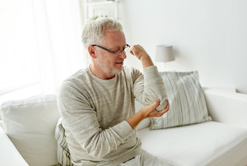 unhappy senior man suffering elbow pain at home
