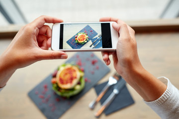 hands with smartphone photographing food