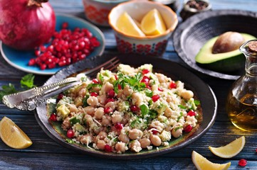 Salad of sprouted chickpeas with couscous, avocado, parsley, olive oil and pomegranate