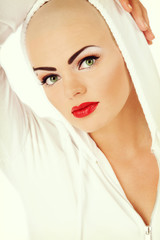 Vintage style portrait of young beautiful skinhead girl with glamorous cat eye make-up and red lipstick