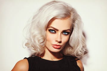 Vintage style portrait of young beautiful platinum blond woman with stylish make-up and curly hair