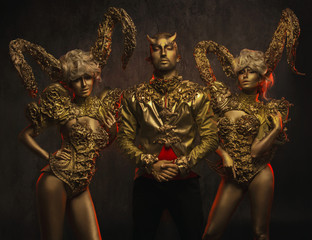 Beautiful devil women with golden ornamental horns and handsome devil man in ornamental jacket on dark background