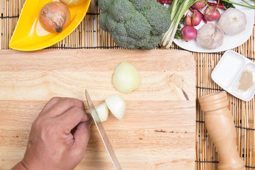 Chef slicing onion on wooden broa
