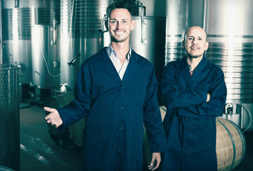 Two smiling men in uniforms standing in winery fermentation comp