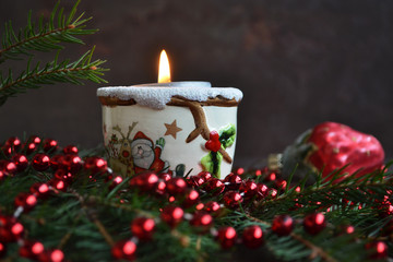Christmas composition with burning candle and festive decoration (with sample text).
