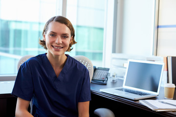 Portrait Of Nurse Wearing Scrubs Sitting At Desk In Office