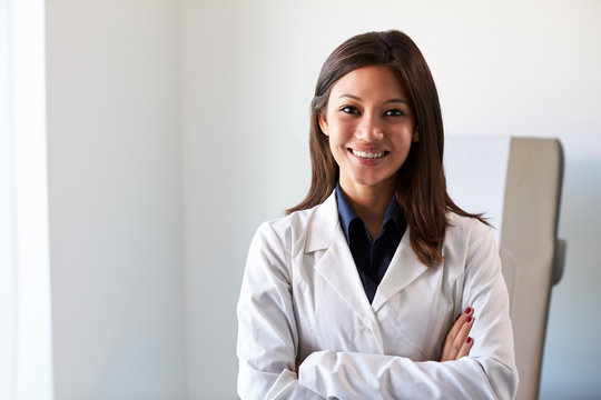 Portrait Of Female Doctor Wearing White Coat In Exam Room