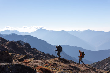 People with Backpacks and trekking Sticks traveling in Mountains