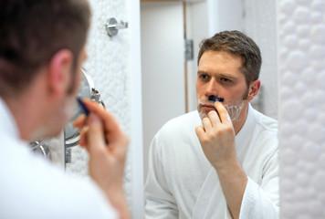 Handsome man shaving in bathroom.
