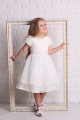 Little girl holding frame. Close up. White background
