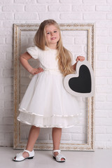 Child in dress with heart and frame. Close up. White background