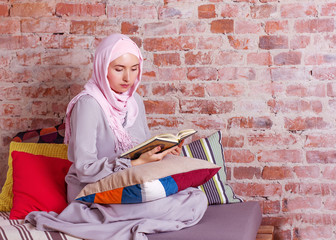 young muslim women reading Quran