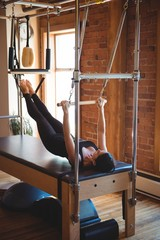 Woman practicing pilates on reformer
