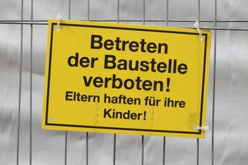 Gelbes Schild Betreten der Baustelle verboten an einem Metallzau