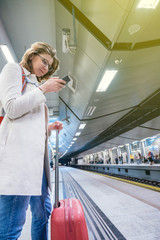 Woman waiting for train and surfing the mobile internet on a smartphone in the Athens subway station with travel luggage bag