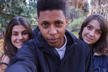 Young people of different races taking a selfie with the smartphone in the park. They are friends and enjoy a nice day outdoors.