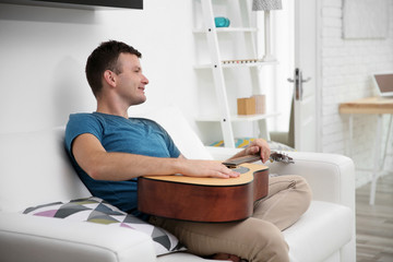 Young man playing the guitar on the sofa in light room