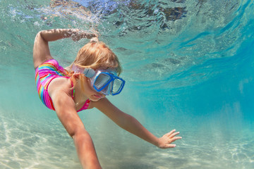 Happy baby girl in snorkeling mask dive underwater with fun in sea pool. Healthy lifestyle, people water sport outdoor adventure, swimming lessons on summer beach family holidays with child