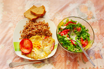 dish for a dinner from boiled buckwheat sausage fried eggs and fresh vegetables