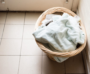 High angle view of towels in wicker laundry basket on rustic tiled floor (selective focus)