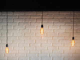Old lighting electric bulb, Retro lamp on a background of a white brick wall. Edison bulb hanging...