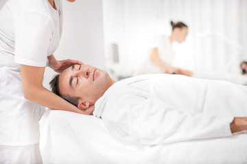 Skillful masseuse massaging male head