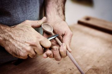 Midsection of carpenter carving wooden spoon with knife in workshop