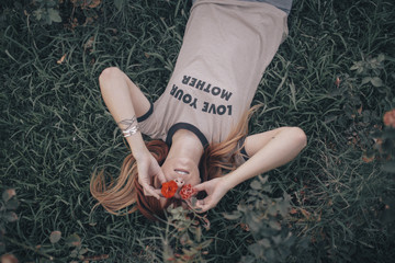 High angle view of woman with flowers lying on grassy field in backyard