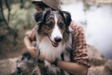 Man with Australian Shepherd in forest