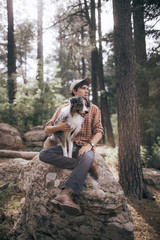 Man with Australian Shepherd sitting on rock in forest