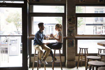 Smiling couple having coffee while talking by glass windows at cafe