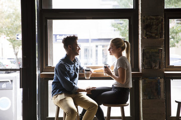 Smiling couple talking while sitting by window at cafe