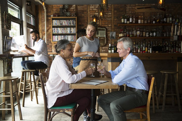Waitress talking to customers sitting at cafe