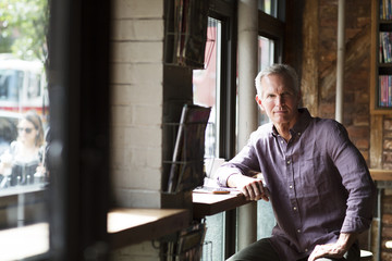 Portrait of mature man sitting at table by windows in cafe
