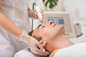 Beautician doing ultrasound cavitation facial massage
