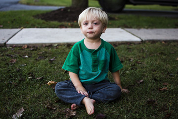 Portrait of boy crying while sitting in backyard