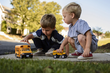 Brothers playing with toys in backyard
