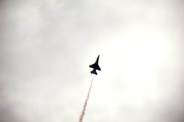 Low angle view of military airplane flying in cloudy sky